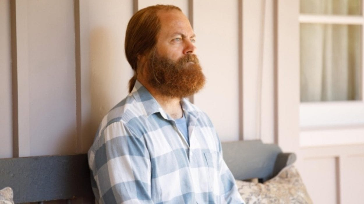 Forest, with his hair tied back and full beard, wearing a blue striped shirt
