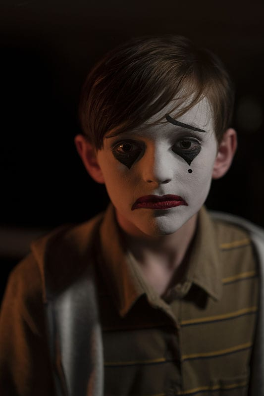 A boy with a sad clown face