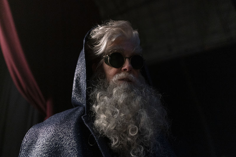 Commander 14 is Richard E. Grant with sunglasses and a very large white beard