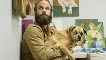 The Guy holds Fomo in front of some paintings of dogs
