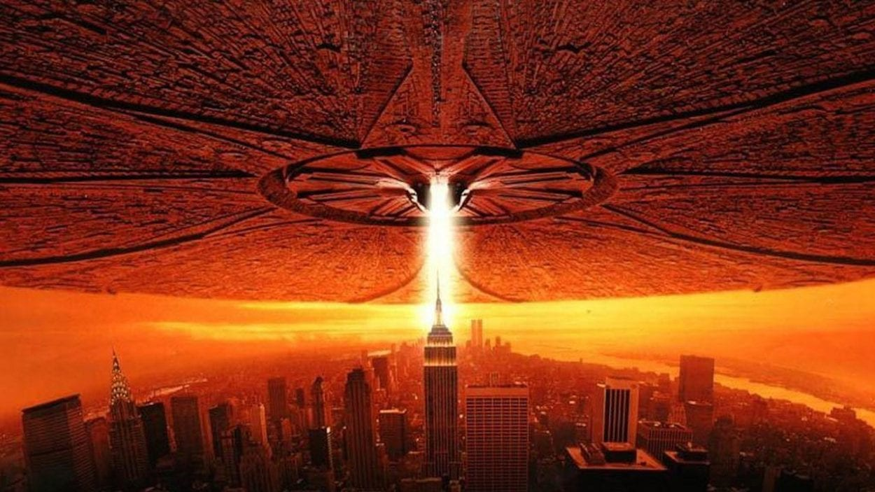 An large alien craft hovering over the Empire State Building with a beam of light coming from it in Independence Day