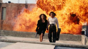 Carolina and El Mariachi walk away from an explosion behind them in an alley below.