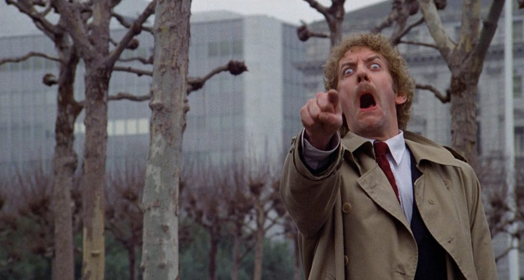 Matthew Bennell, wearing a trenchcoat in a park pointing with a look of terror on his face in Invasion of the Body Snatchers.