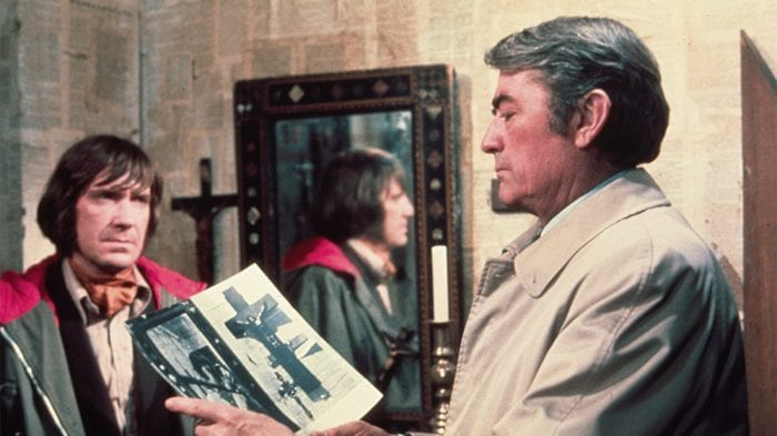 In a room wallpapered with bible pages, Keith Jennings looks on as Robert Thorn studies two photographs.