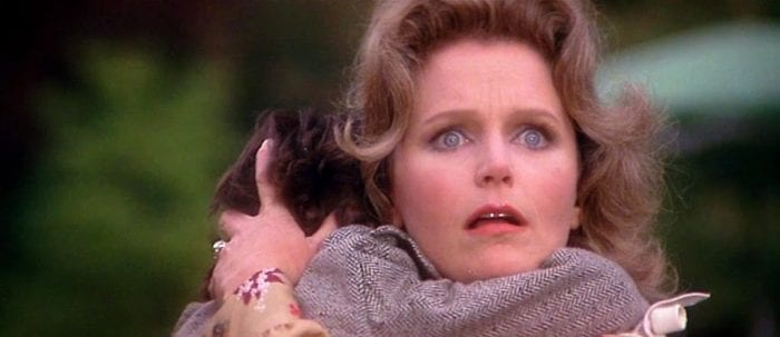 Outside, Katherine Thorn clutches Damien in her arms while looking on in horror.