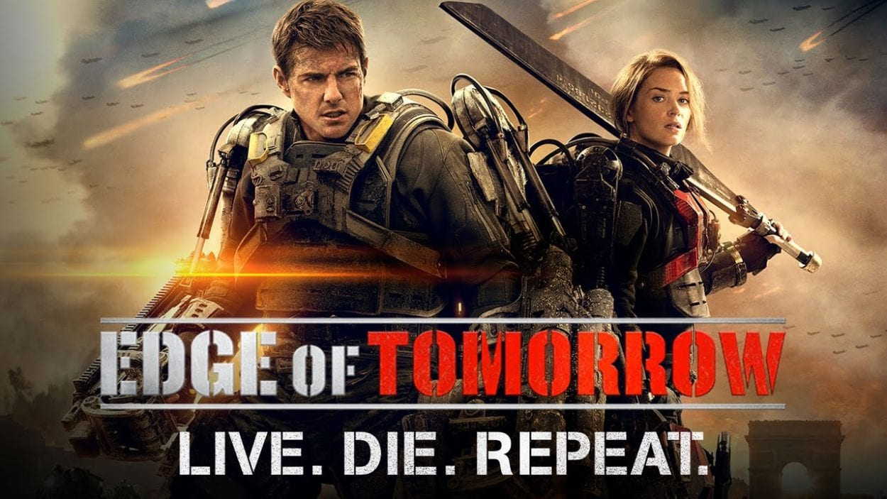 Cage and Rita stand back to back wearing exo-skeletons in Edge of Tomorrow