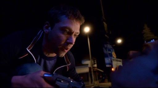 Jake points a gun at David taking him hostage