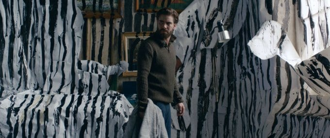 Matt holds a piece of blanket while surrounded by painted, destroyed walls
