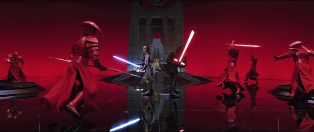 Rey and Kylo Ren fight a bunch of guys in red armor in a throne room.