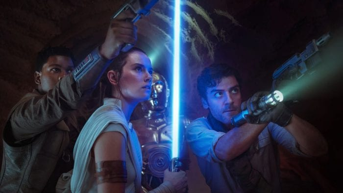 Rey, Poe Dameron, and Finn look up at some unknown threat. C3PO is in the background.