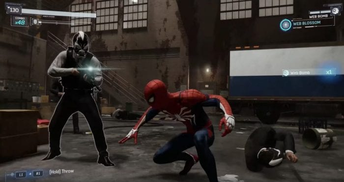 Spidey crouches, preparing to attack a thug wielding an assault rifle.