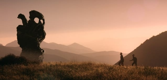 Two silhouetted figures walking a hill towards a strange rock formation