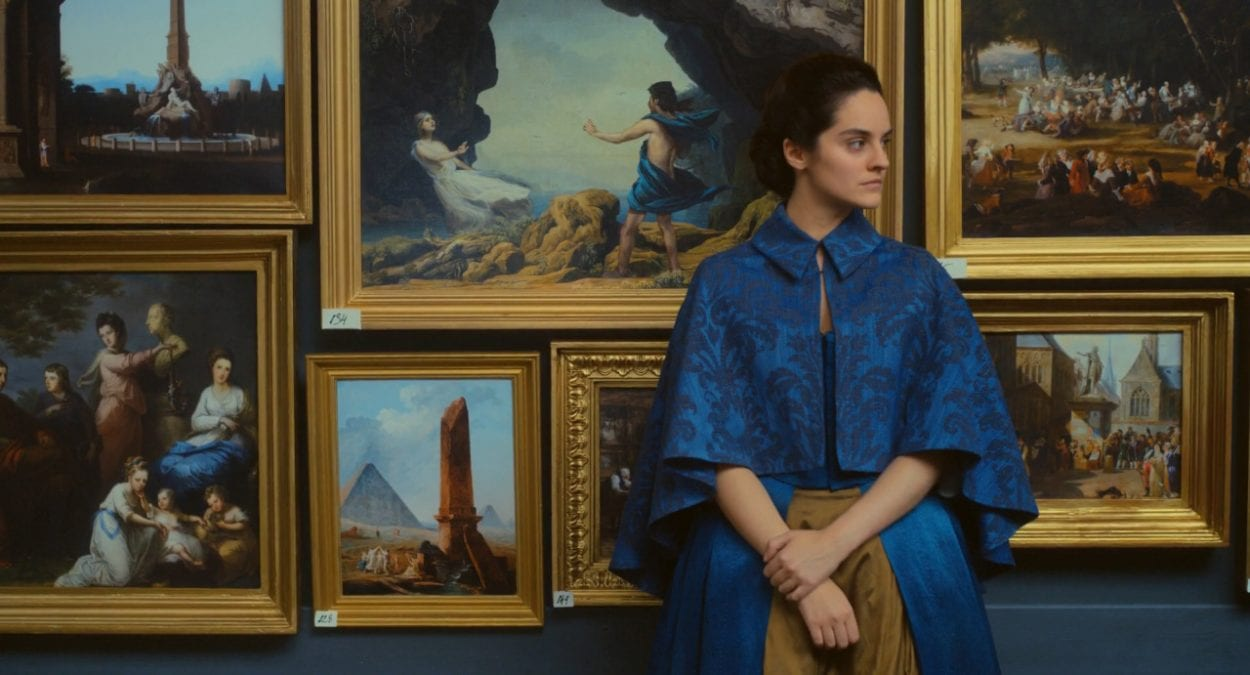 Marianne stands in a museum, with her painting or Orpheus and Eurydice behind her