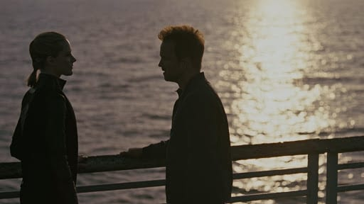 Dolores and Caleb face each other at the pier, the water behind them and the sun setting