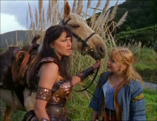 An early days (S1) shot of Xena and Gabrielle, standing with Argo, Xena's horse