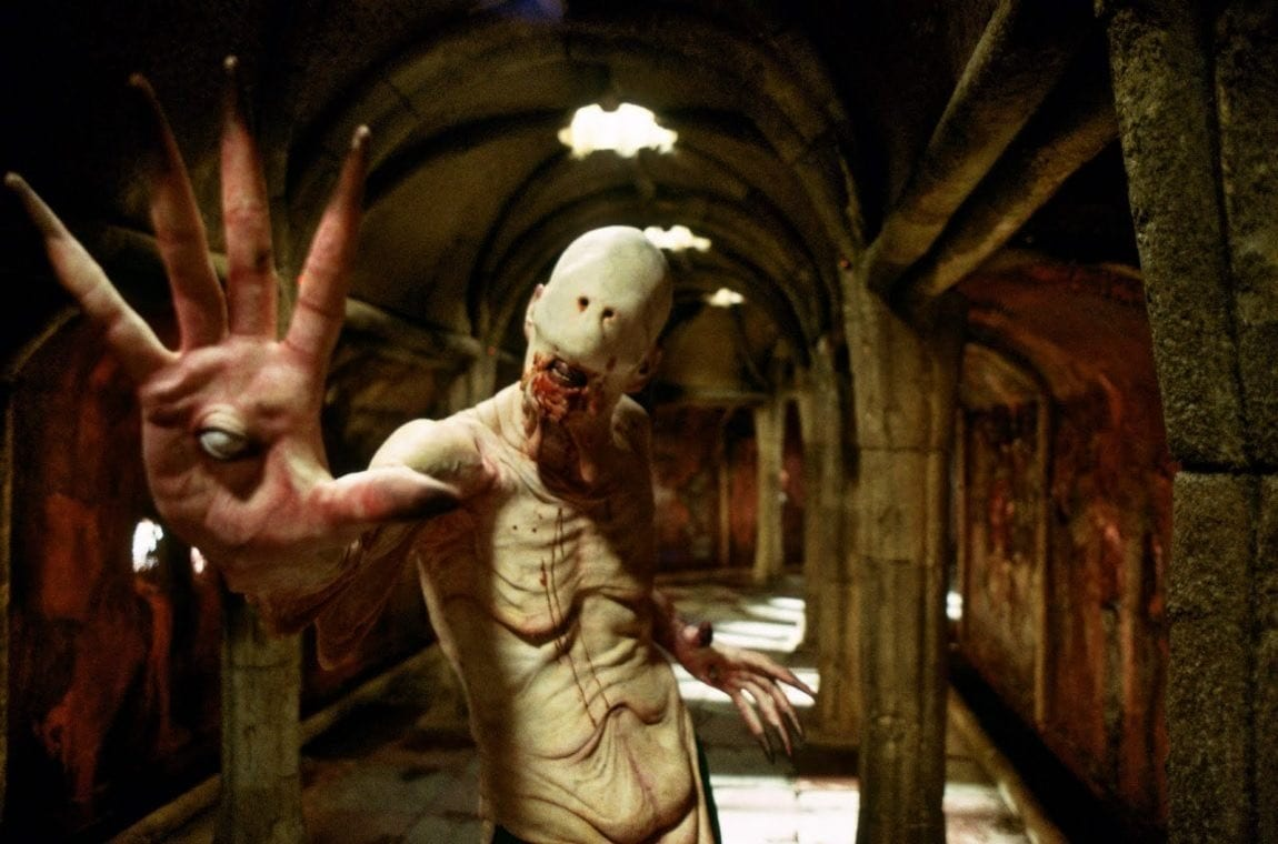 The Pale Man stretches out a grotesque hand with an eyeball in the palm at the camera
