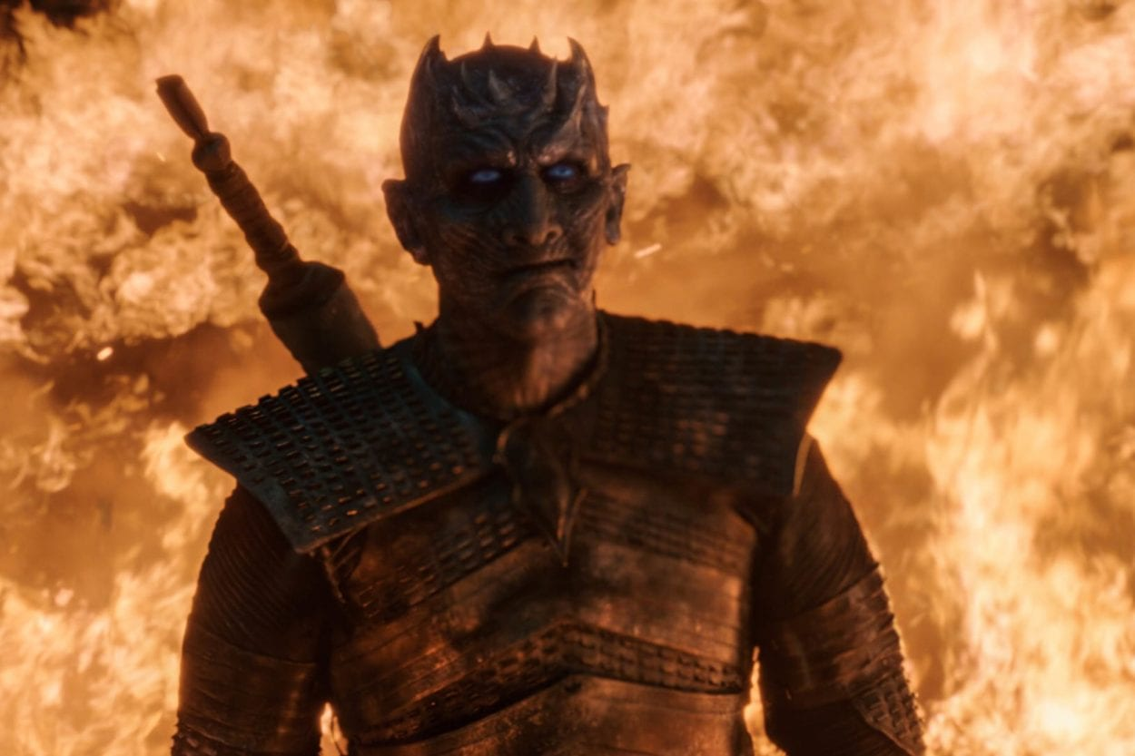 The Night King stands with flames in the background, looking up with a smirk on his face