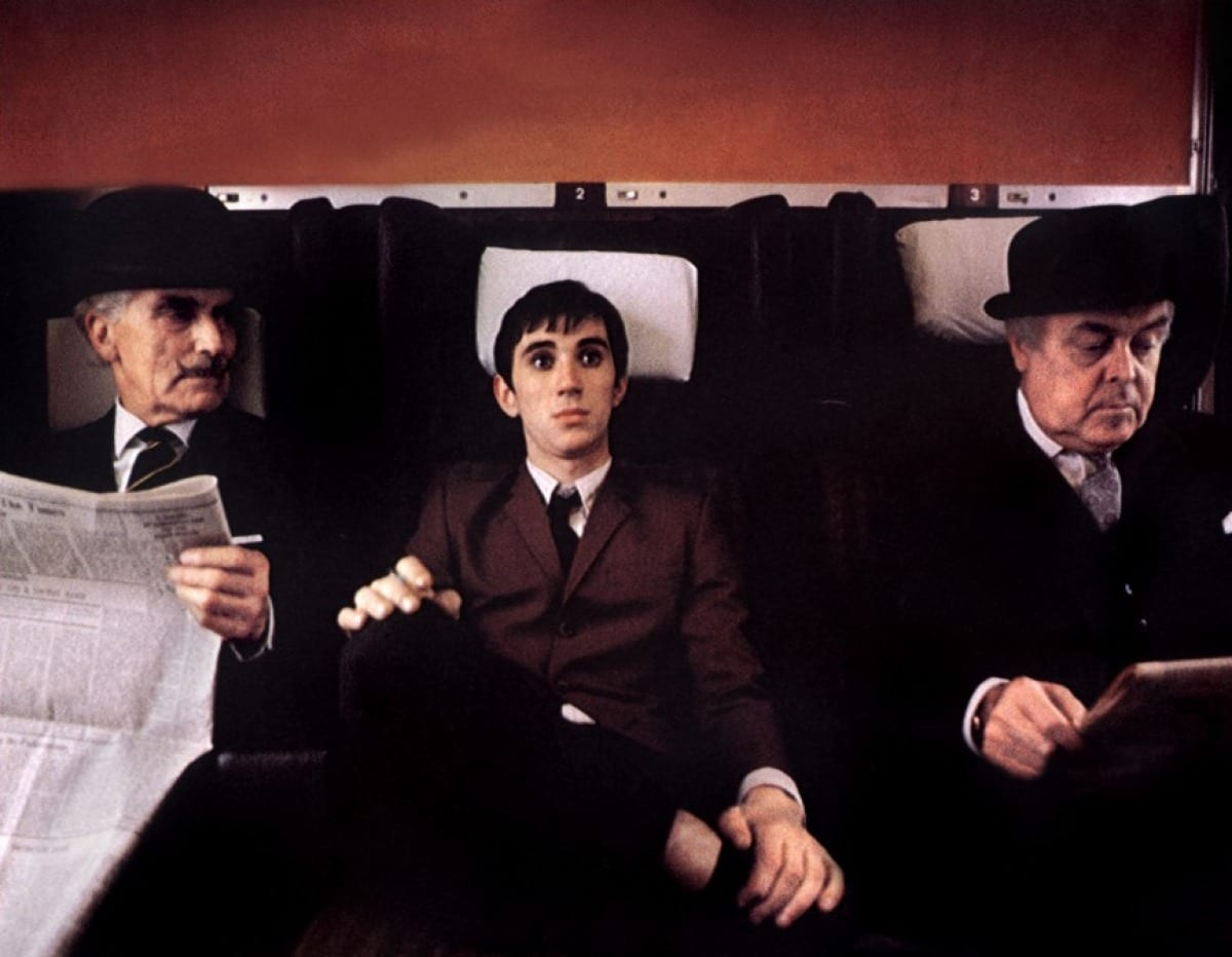An out-of-sorts Jimmy sits between two stuffy businessmen on the train