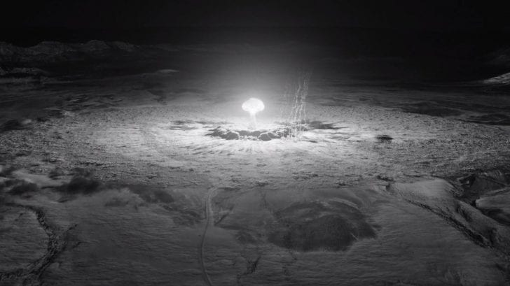 A black and white look at a nuclear mushroom cloud explosion from extremely far away.