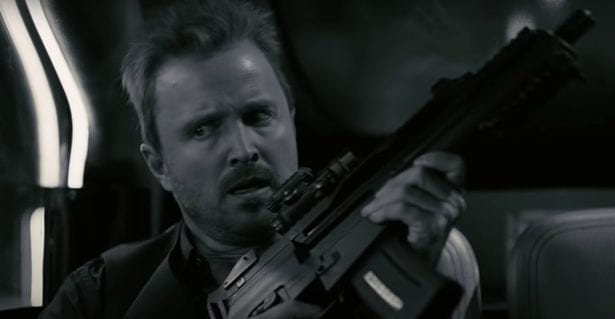 Caleb clutches a heavy duty machine gun whilst lit in black and white