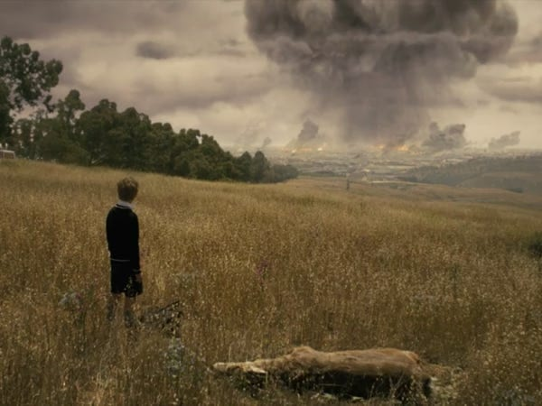 A young Serac watches from a grassy hillside as a massive grey plume of smoke erupts from Paris