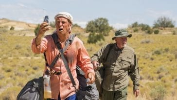 Jimmy holds up his cell phone to get reception in the desert as Mike follows behind him