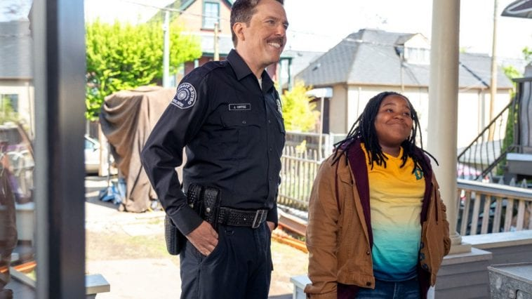 Officer John Coffee and Kareem Manning attempt to smile and play nice on a porch for a visitor.