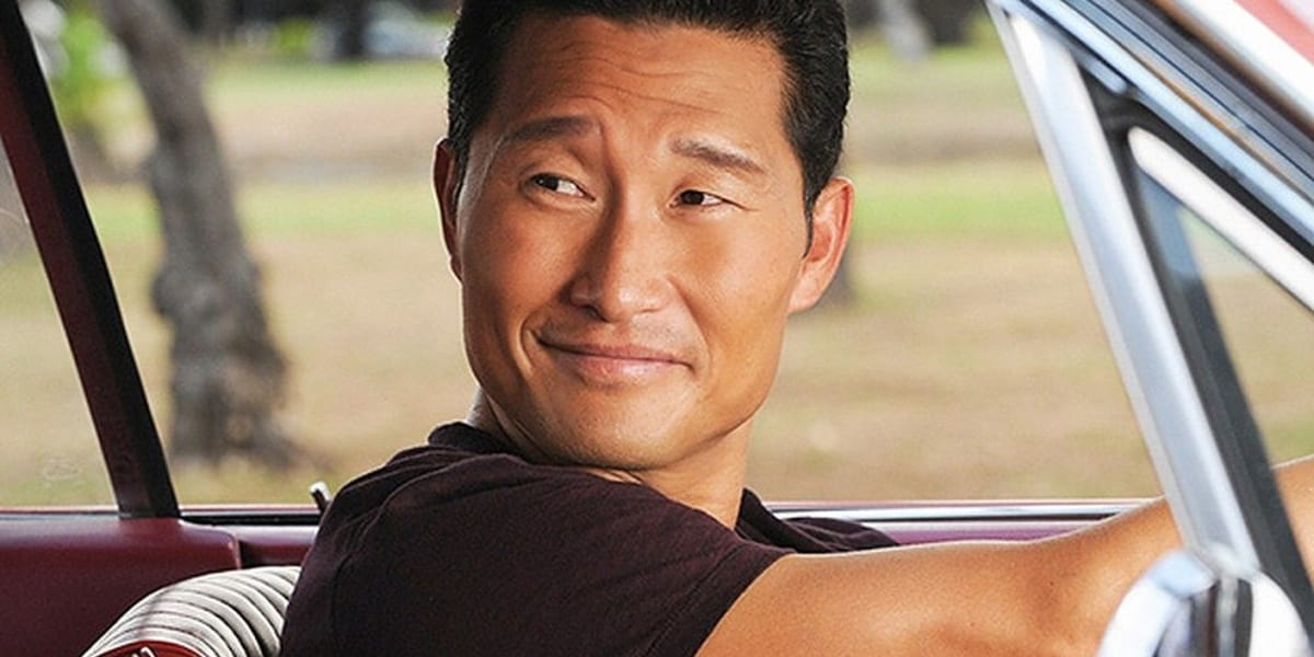 Chin in Hawaii Five-0 looking to his right with a small smile with his arms outstretched, hands on the steering wheel inside a car