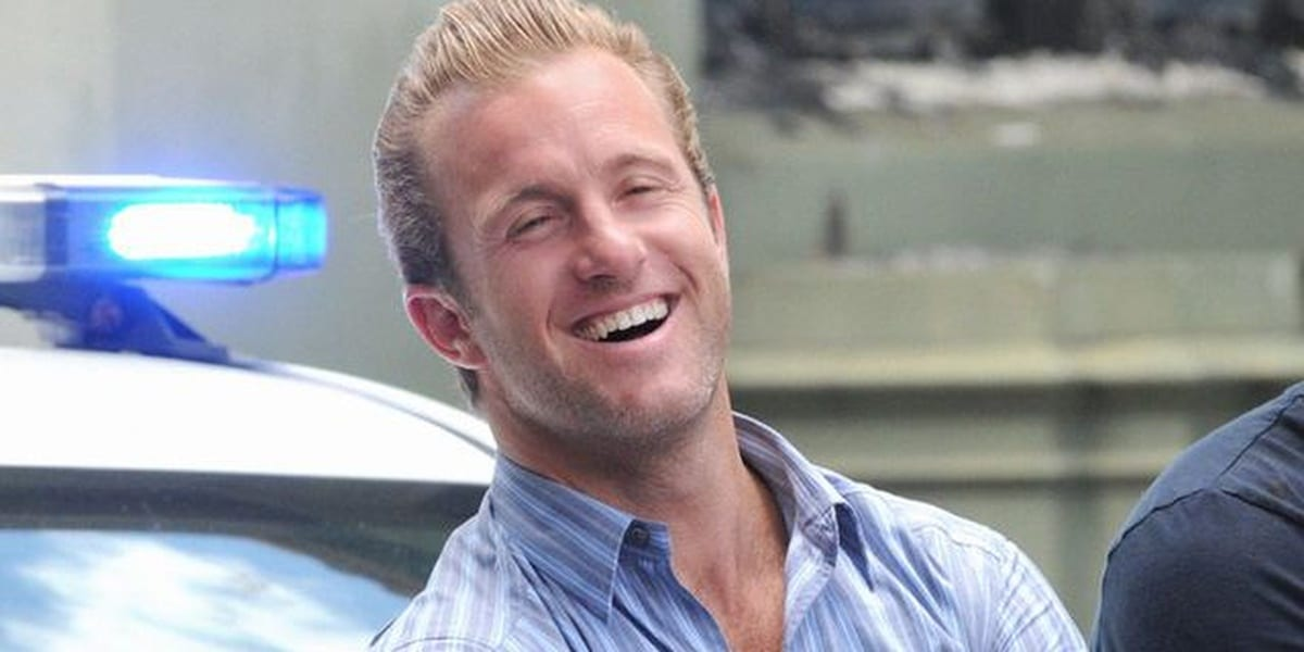Danny Williams leaning against a cop car and laughing in Hawaii Five-0