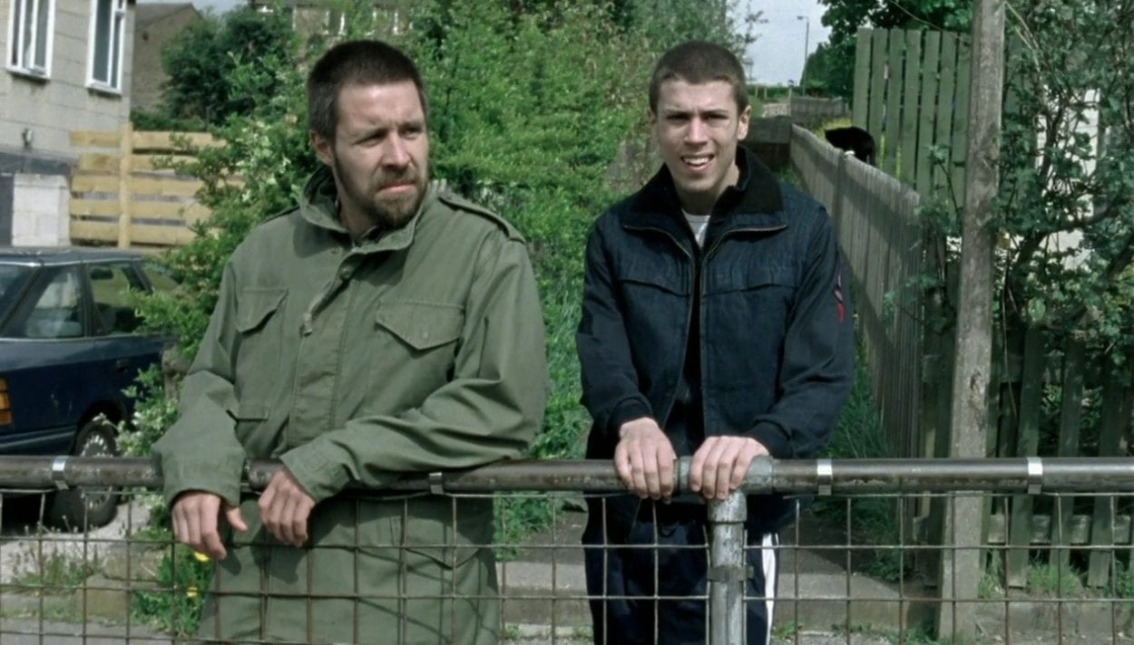 Richard and Anthony stand side by side in conversation in front of a railing.