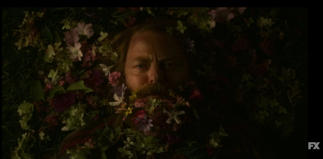 A sad-looking Forest surrounded by flowers in Devs S1E6