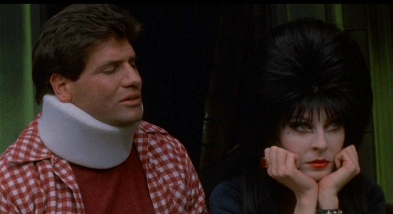 Sitting on Elvira's front porch, Bob wears a neck brace while Elvira holds her head in her hands.