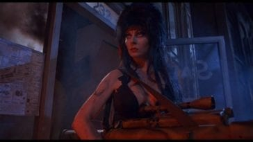 Elvira stands alone holding a machine gun outside, at night.