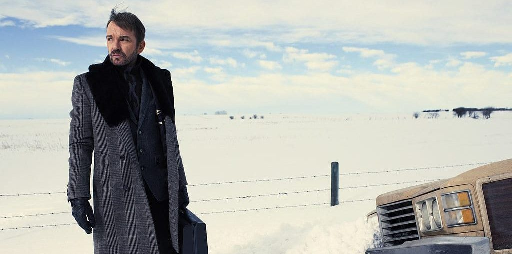 Lorne Malvo played by Billy Bob Thornton, stands in the snow next to a car with a briefcase