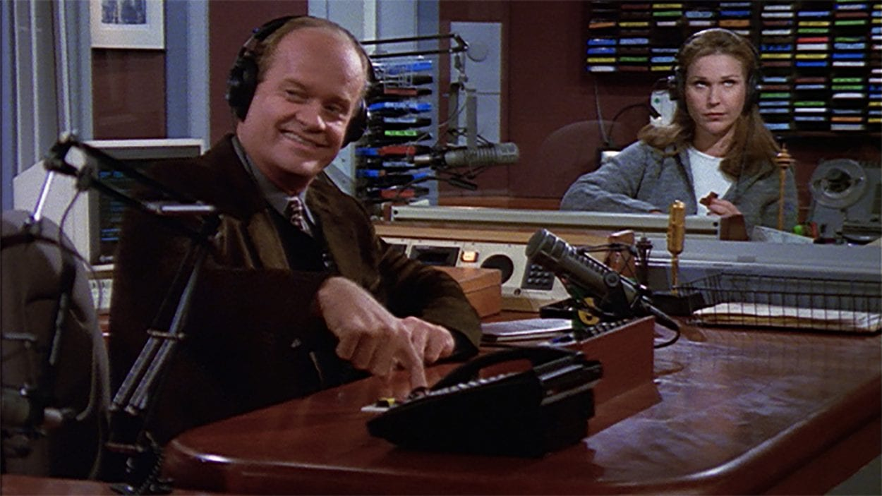 Frasier smiles in the recording studio while Roz rolls her eyes in the beackground