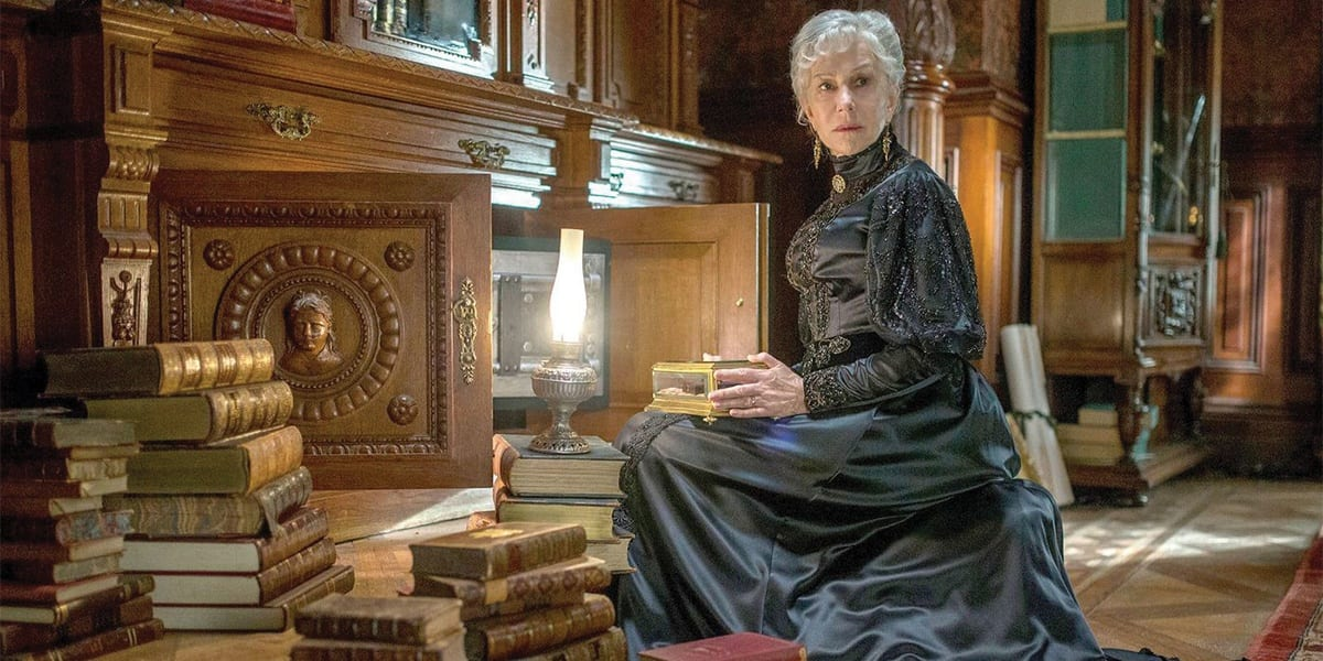 Helen Mirren as Sarah Winchester, sitting and looking to her right somewhat fearfully with books in stacks around her