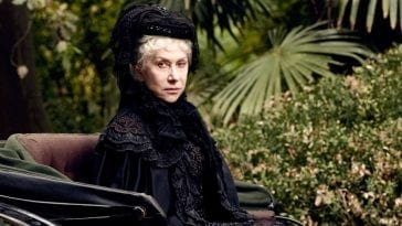 Helen Mirren sitting in a carriage staring directly at the photographer dressed in black with green lush trees in the background in Winchester