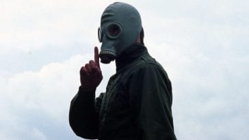 Richard wearing a gas mask with his finger to his mouth in a shushing motion