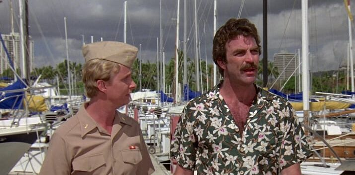 Magnum talks to a man in uniform as they walk around a marina