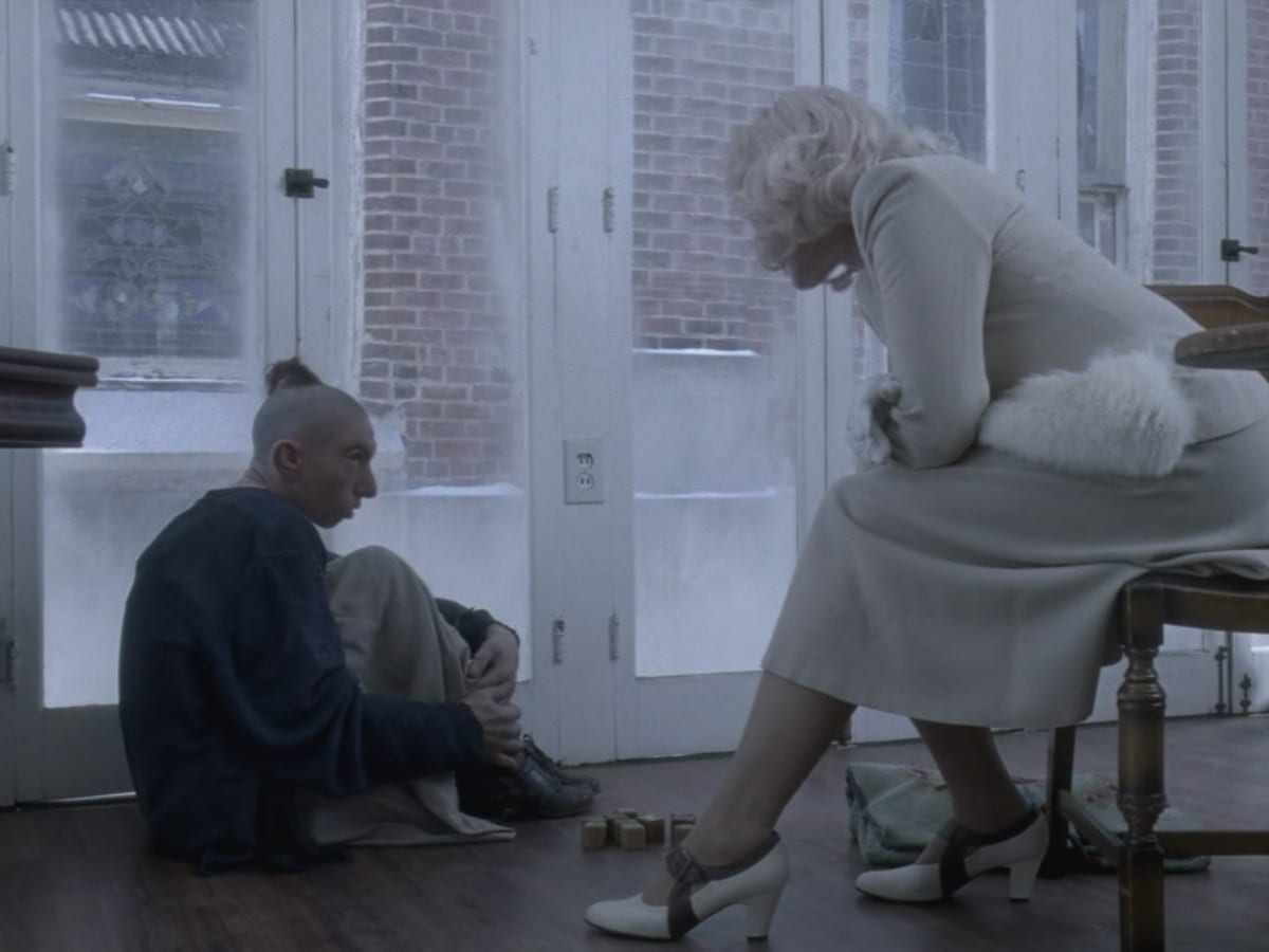 Pepper sits on the floor, as Elsa sits in a chair to talk to her