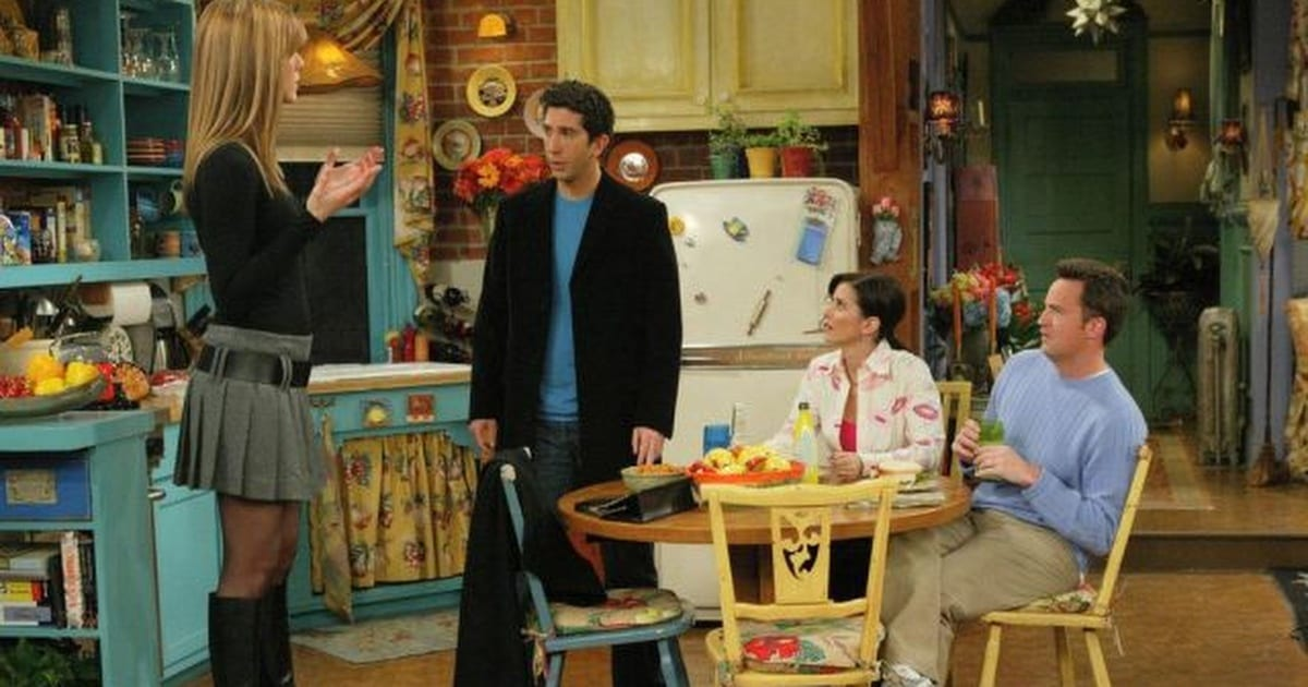 Rachel standing with her back to the camera looking at Monica and Chandler, Chandler and Monica looking in shock at Ross, Ross looking to his left as though expecting someone else to come through the door