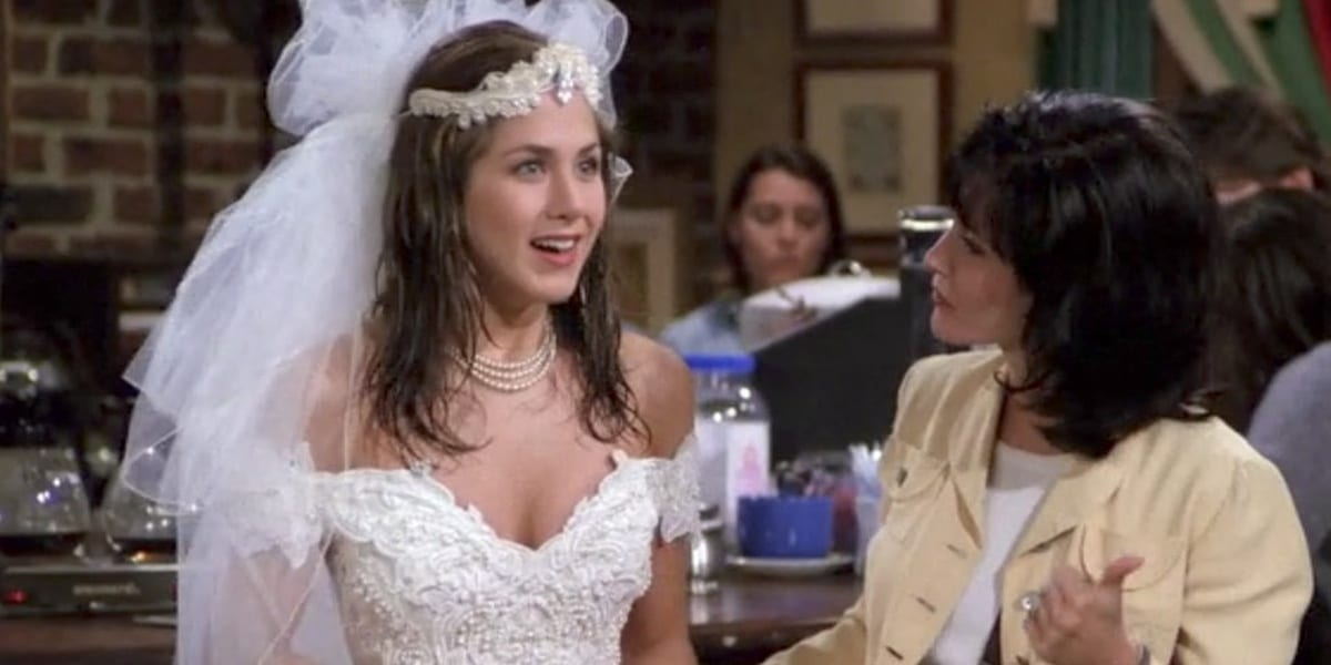 Rachel Green in the Friends pilot wearing a wedding dress with a smile looking ahead with Monica's profile shown looking at Rachel