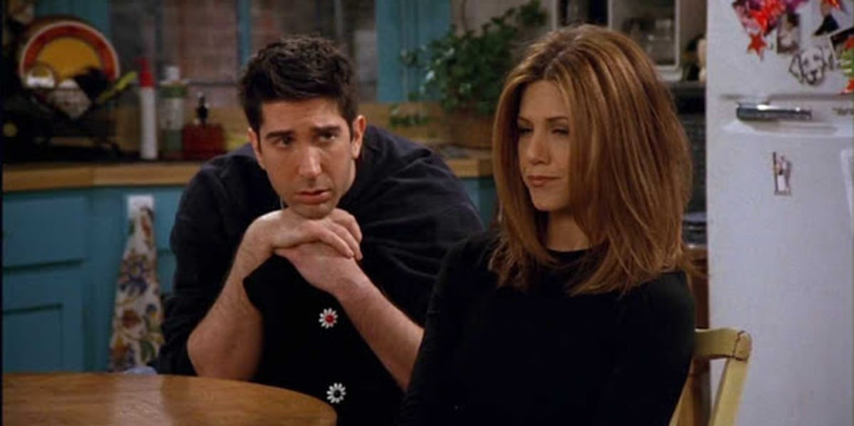 Rachel looking hurt as she stares ahead, Ross sits behind her, hands folds, looking at her sadly but hopefully in Friends