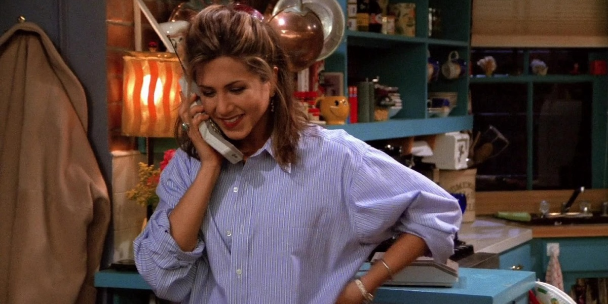 Rachel looking down, smiling, holding a phone to her ear in one hand and her other hand on her hip in Friends