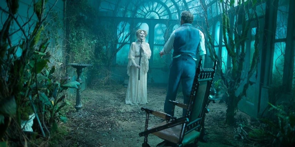 Eric stands with his back to the camera, his wife Ruby in front of him holding a gun below her chin as they stand in an overgrown greenhouse in Winchester