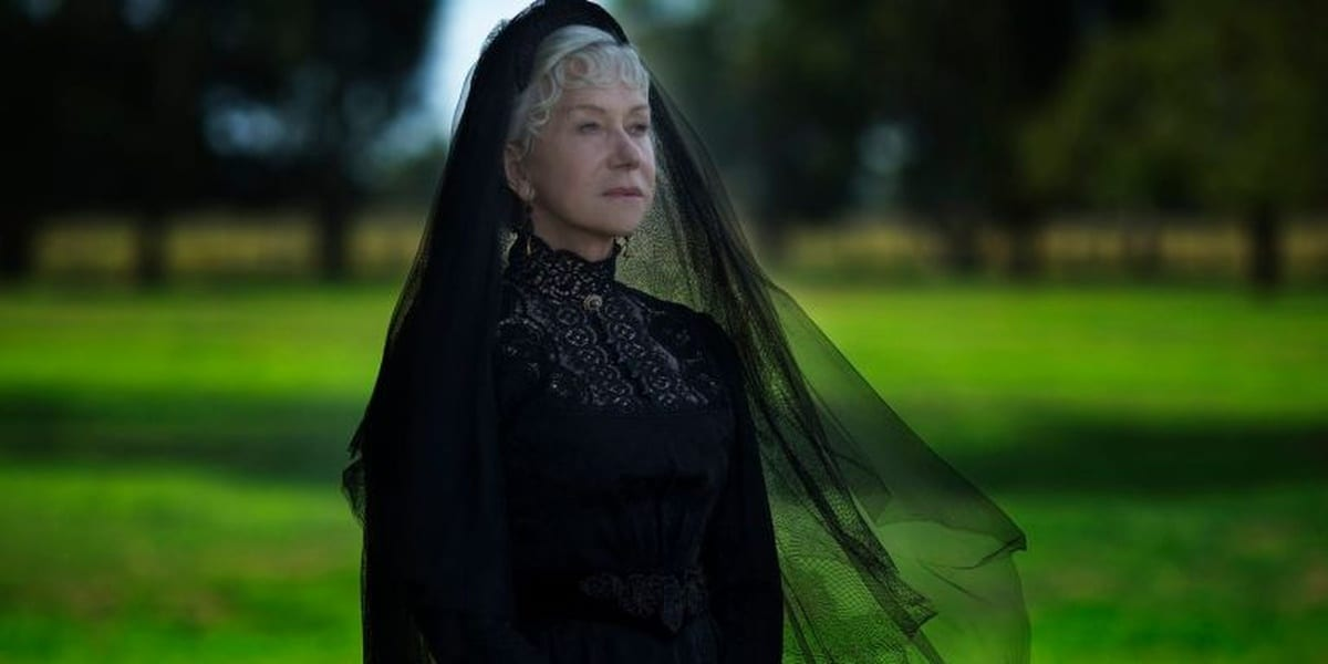 Sarah Winchester, as shown at an angle, looking ahead of her with resolve with grass and trees in the background and wearing all black