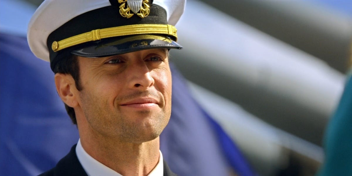 Steve McGarrett wearing a navy uniform smiling and looking in front of him, the picture at an angle