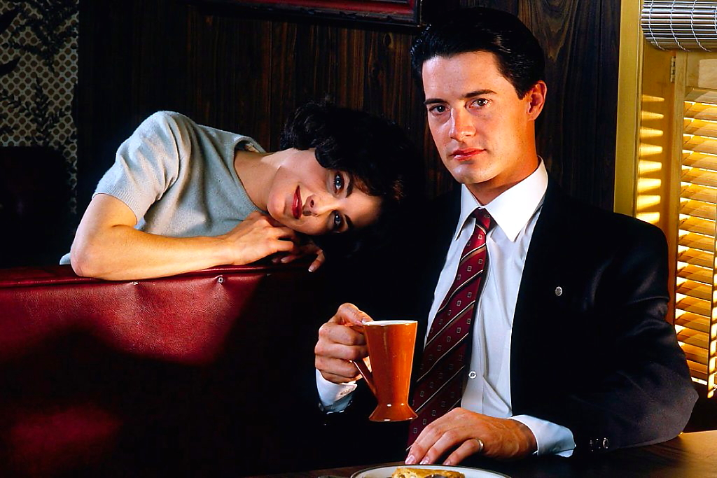 Agent Cooper and Audrey horney sit in a booth of the Double R diner