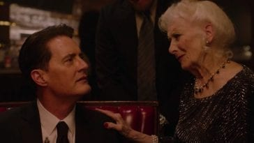 An elderly woman places her hand on the shoulder of a sitting Dale Cooper.