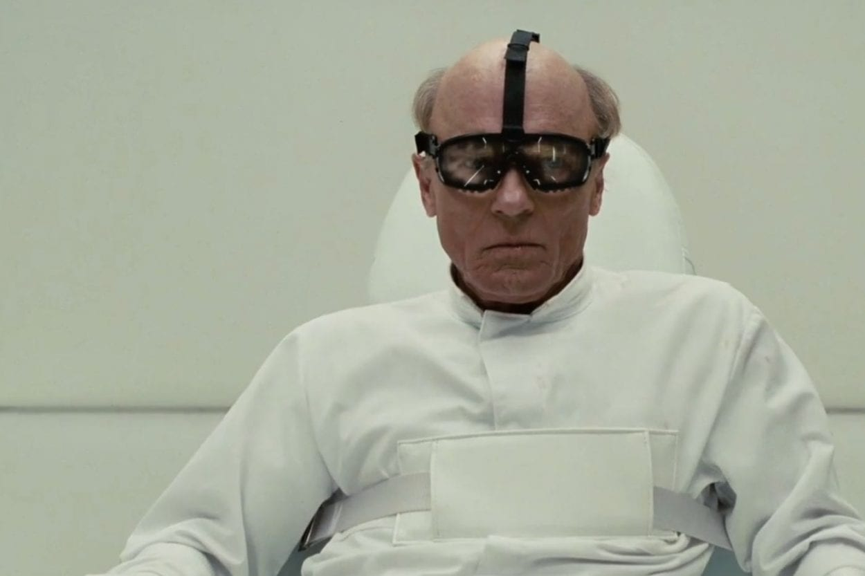 William is strapped to a chair in a psychiatric institution, wearing goggles